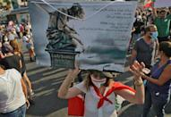 A woman holds a sign condemning officials for the 2020 Beirut port blast, on the first anniversary of the explosion