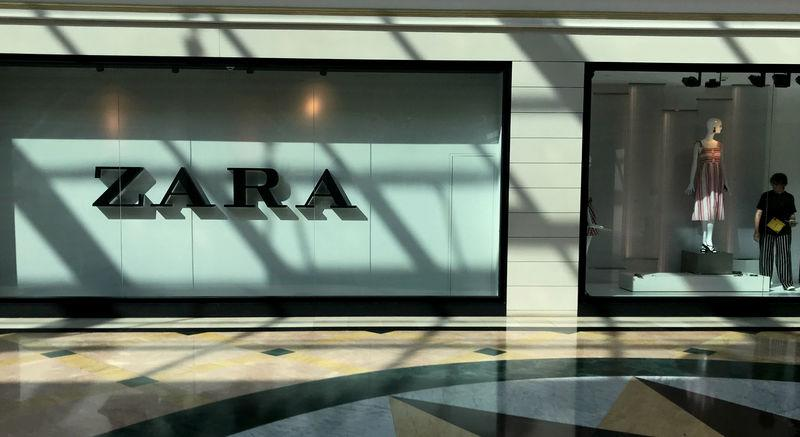 A worker decorates the shop window of Inditex's main brand Zara in a shopping mall in Majadahonda