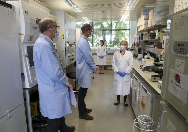 Britain's Prince William, center, wears a mask as he meets scientists during a visit to the manufacturing laboratory where a vaccine against COVID-19 has been produced, at the Oxford Vaccine Group's facility at the Churchill Hospital in Oxford, England, Wednesday, June 24, 2020. The royal was given a tour Wednesday of the manufacturing laboratory where the experimental vaccine has been produced. The trials began Apr.23 and 10,000 people in the U.K are in the process of being vaccinated to assess the potential success of the treatment. (Steve Parsons/Pool photo via AP)