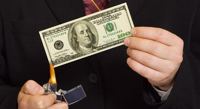 A person holding a one hundred dollar bill and setting it on fire with a lighter.
