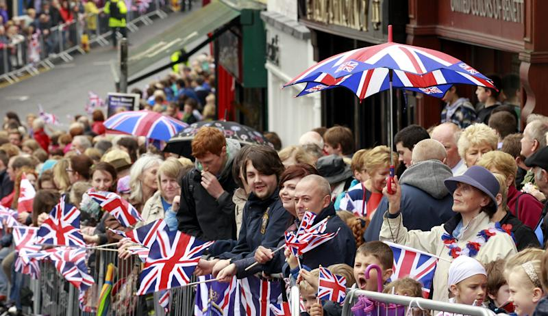 Members of the public wait to catch a view of Britain's Queen Elizabeth II outside a Service of Thanksgiving in Saint Macartin's Cathedral in Enniskillen, Northern Ireland, Tuesday, June 26, 2012.  The Queen arrived in Northern Ireland for a two day visit to mark the Queen's Diamond Jubilee. (AP Photo/Peter Morrison)