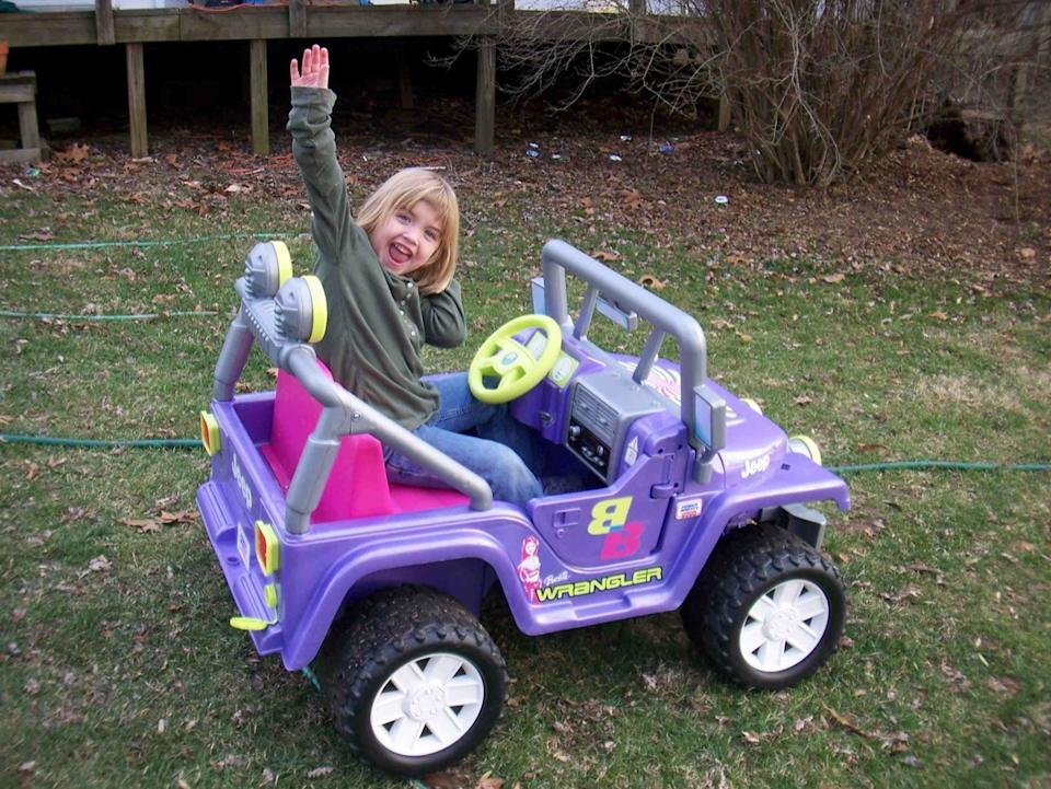 little girl driving a barbie jeep