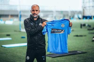 Manchester City manager Pep Guardiola shows off matchday shirt for Premier League return
