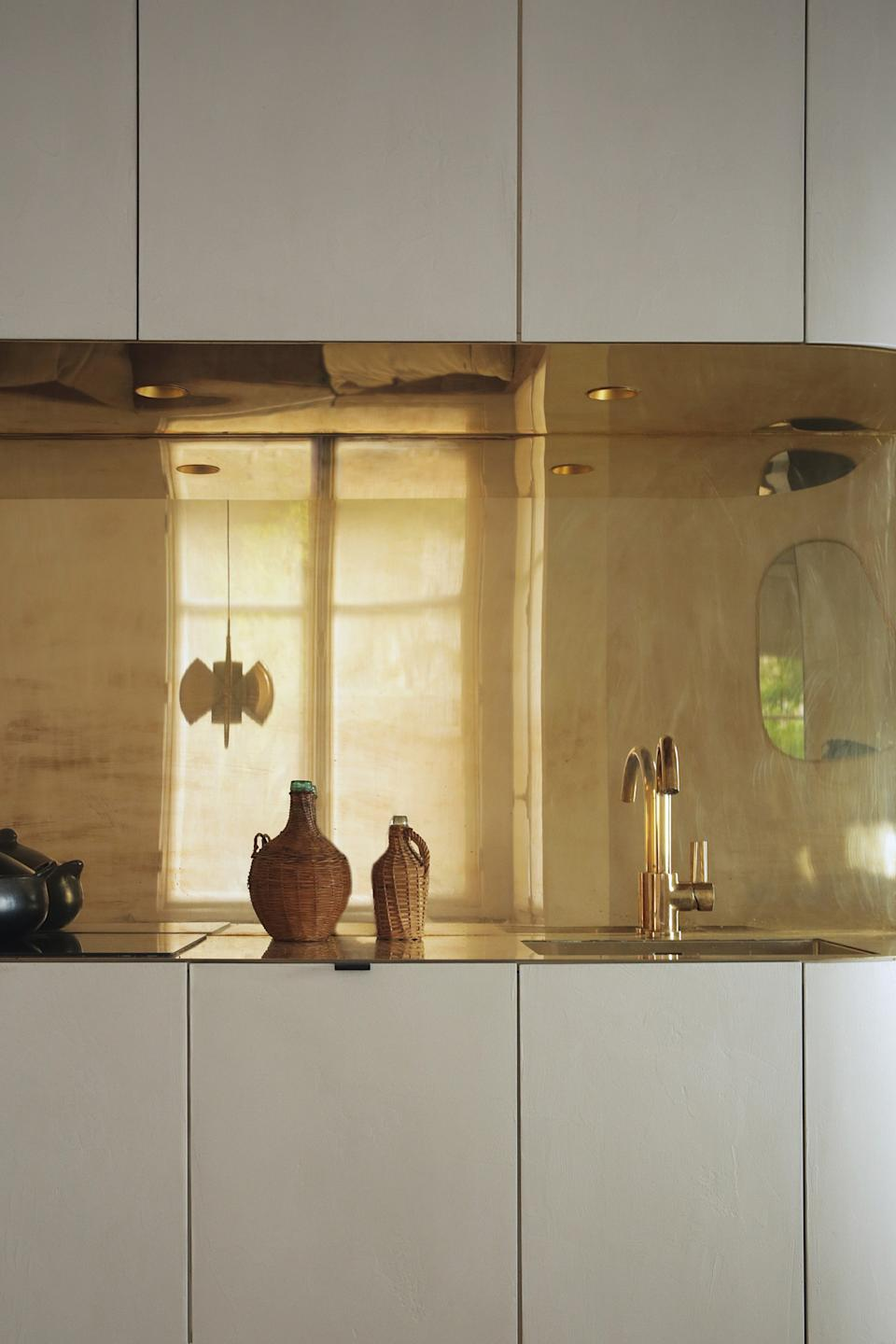 """<div class=""""caption""""> The metallic backsplash makes a huge impact in the tiny apartment, reflecting light and giving the space an elegant quality. </div>"""