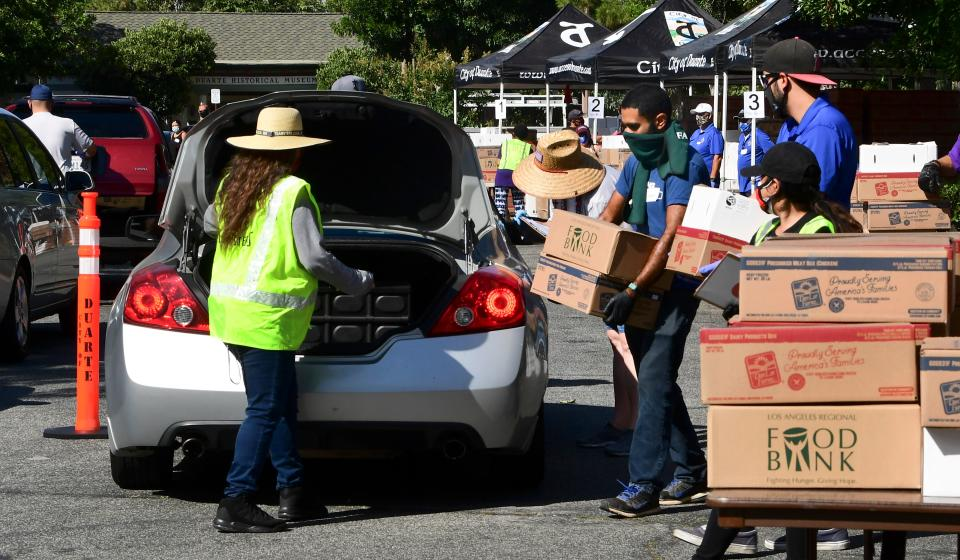 Volunteers help load a vehicle with boxes of food at a food bank in the Los Angeles County city of Duarte, California on July 8, 2020 as the record for most coronavirus cases in a single day is set in California. - Oxfam, the confederation of 19 charitable independent organizations focusing on the alleviation of global poverty, is due to release an embargoed report on July 9 suggesting that COVID-19 may kill more people worldwide due to hunger than the illness itself. (Photo by Frederic J. BROWN / AFP) (Photo by FREDERIC J. BROWN/AFP via Getty Images)
