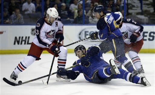 St. Louis Blues' David Backes, center, manages to reach the puck and score as he falls to the ice while teammate Jaden Schwartz, right, and Columbus Blue Jackets' Adrian Aucoin, left, look on a during the second period of an NHL hockey game on Friday, April 5, 2013, in St. Louis. (AP Photo/Jeff Roberson)