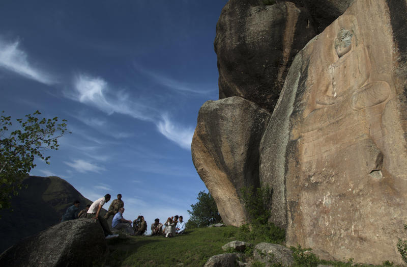 """In this May 24, 2012 photo, people sit near a sculpture of the Buddha whose face was destroyed by Taliban fighters at Jahanabad, Pakistan in the Swat valley. When the militants detonated the face off the towering, 1,500-year-old rock carving in northwest Pakistan in fall 2007, it fell to an intrepid Italian archaeologist to come to the rescue. Swat was once an important center of Buddhist culture and trade. The monk credited with introducing Buddhism to Tibet, Padmasambhava, was born in Swat. (AP Photo/B.K. Bangash) PART OF A SIX-PICTURE PACKAGE FOR """"PAKISTAN FIXING BUDDHA"""""""