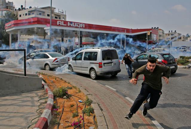 <p>Palestinians run away from tear gas shot at them by Israeli forces during a protest in Ramallah, in the occupied West Bank, on May 15, 2018. (Photo: Abbas Momani/AFP/Getty Images) </p>