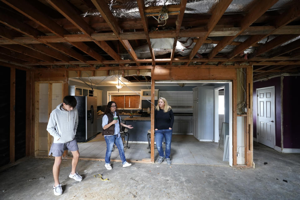 Christi, center, and Brandy Monticello, walk through their heavily damaged and gutted home, with their son Brennan Ash, in the aftermath of Hurricane Laura and Hurricane Delta, in Lake Charles, La., Friday, Dec. 4, 2020. (AP Photo/Gerald Herbert)