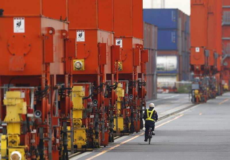A man rides a bicycle past containers at a port in Tokyo