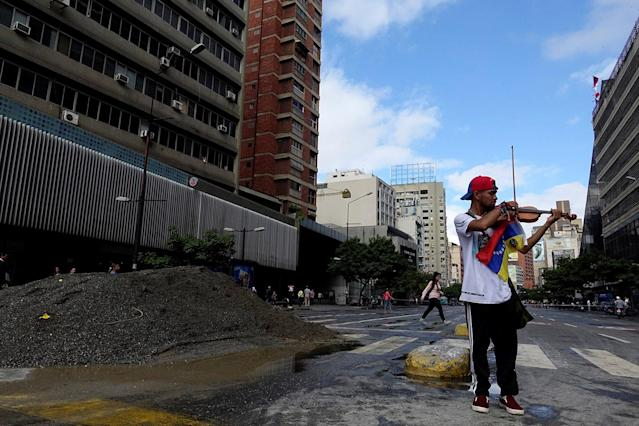 <p>Venezuelan violinist Wuilly Arteaga plays the violin next to a pile of sand used by protesters to block the street during a protest against Venezuelan President Nicolas Maduro's government in Caracas, Venezuela July 18, 2017. (Photo: Carlos Garcia Rawlins/Reuters) </p>