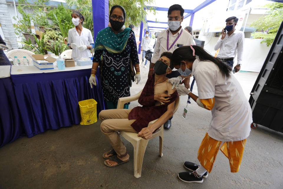 A physically disabled man gets a dose of Covishield, Serum Institute of India's version of the AstraZeneca COVID-19 vaccine, during a drive through vaccination organized for disabled people in Ahmedabad, India, Saturday, June 12, 2021. (AP Photo/Ajit Solanki)