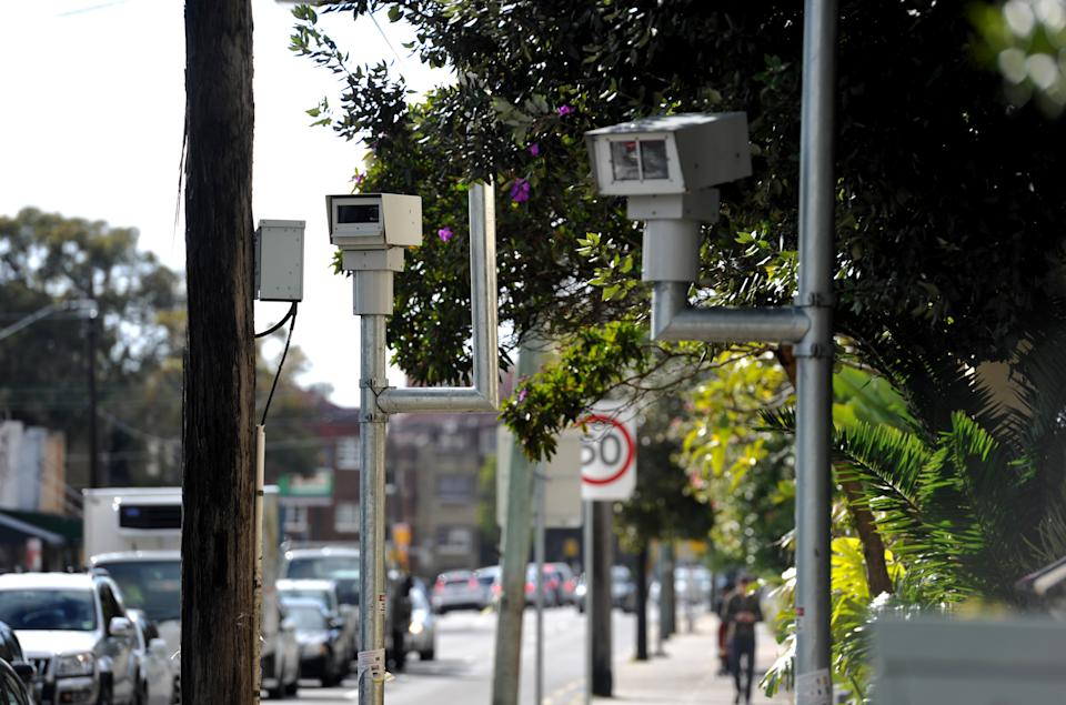 Picture of speed cameras on a Sydney road, with traffic passing by.