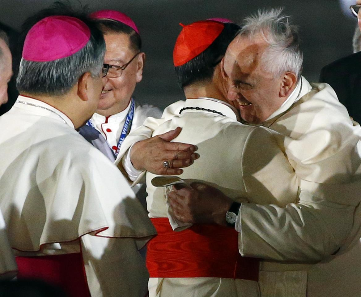 Pope Francis (R) embraces Philippine Cardinal Luis Antonio Tagle upon his arrival at Villamor Air Base in Manila, for a state and pastoral visit, January 15, 2015. Tens of thousands of people lined the streets of the Philippines capital of Manila on Thursday to welcome Pope Francis on his first visit to Asia's largest Catholic nation amid one of the biggest security operations in the country's history. REUTERS/ Stefano Rellandini  ( PHILIPPINES - Tags: RELIGION POLITICS)