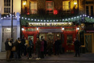 FILE - In this March 17, 2020 file photo people stand drinking outside the Coach & Horses pub on Saint Patrick's Day in the Covent Garden district of central London, which is a popular tourist area. (AP Photo/Matt Dunham, File)