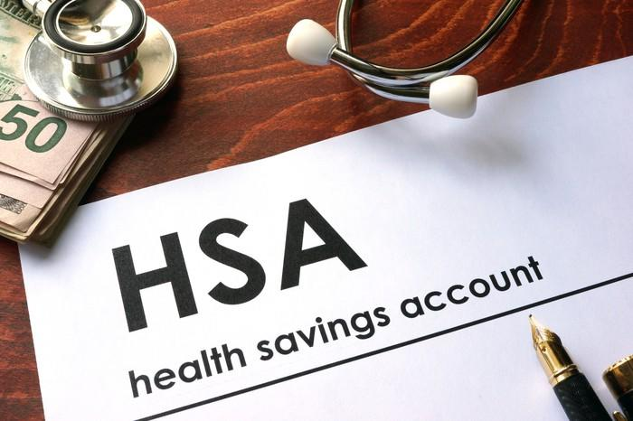 HSA written on a paper near wad of bills and a stethoscope