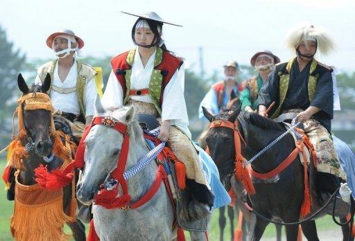 A young woman (C) clad in samurai costume rides her horse during a parade at the annual Soma Nomaoi festival in Minamisoma. The sound of conch horns echoed through the streets with tens of thousands of visitors coming out to see the ancient show of military pomp and pageantry featuring about 400 hundred horses