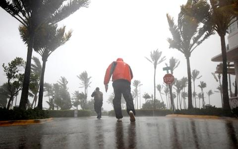 People walk along a street in South Beach as Hurricane Irma arrives at south Florida, in Miami Beach - Credit: CARLOS BARRIA