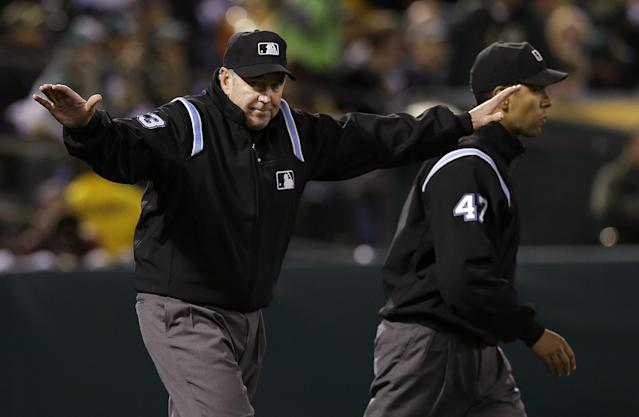 Umpire Mike Winters, left, signals safe next to umpire Mark Wegner (47) as he reverses the ruling that Cleveland Indians' Mike Aviles was out stealing second base against the Oakland Athletics after Indians manager Terry Francona challenged the call during the sixth inning of an MLB American League baseball game in Oakland, Calif., Wednesday, April 2, 2014. (AP Photo/Jeff Chiu)