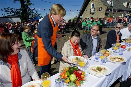 Crown Prince Willem-Alexander serves a meal to spectators during the annual Queens day in Veenendaal