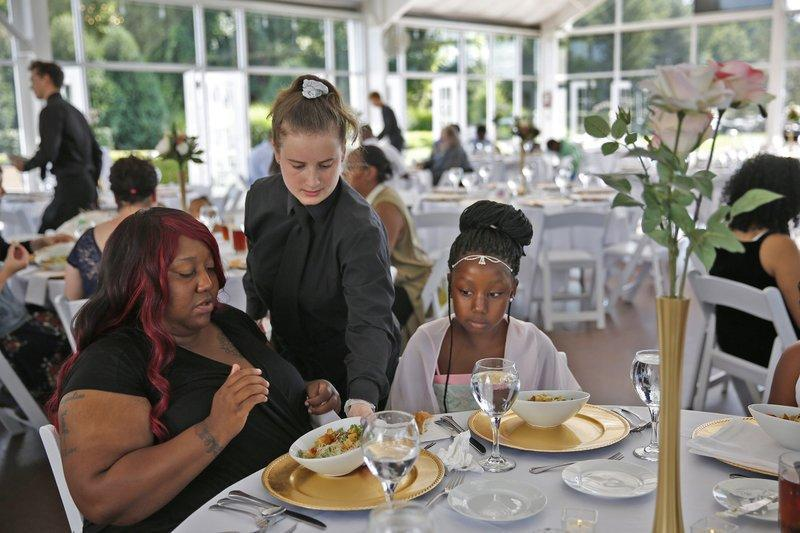 Waitress Katelin Decraene gives Trishell Crawford and her daughter Jacqueline Crawford salads at the reception: Kelly Wilkinson/The Indianapolis Star via AP