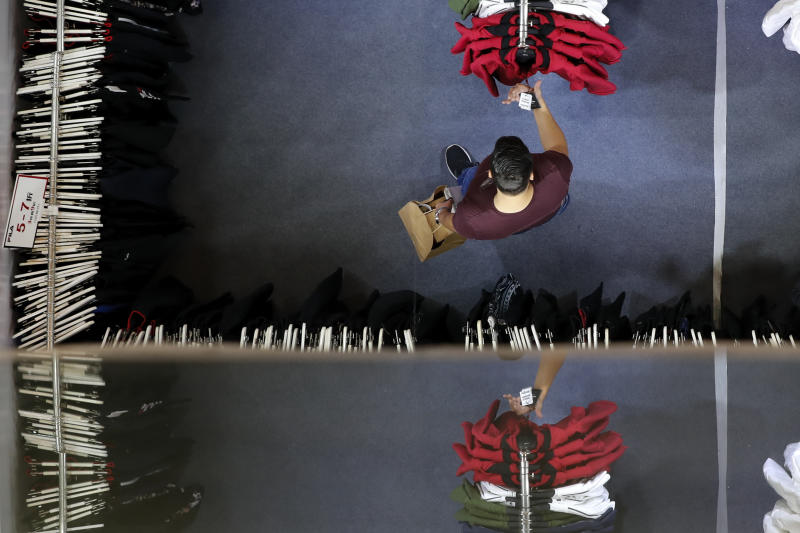 A man checks clothing price tags at a fashion retailer store having a promotion sale at a shopping mall in Shenzhen, China's Guangdong province, Friday, Nov. 1, 2019. Chinese leaders are counting on consumers to power the economy, replacing trade and investment as Beijing fights a tariff war with Washington. But shoppers are jittery about possible job losses and are tightening their belts, hurting sales of cars, real estate and other big-ticket items. (AP Photo/Andy Wong)