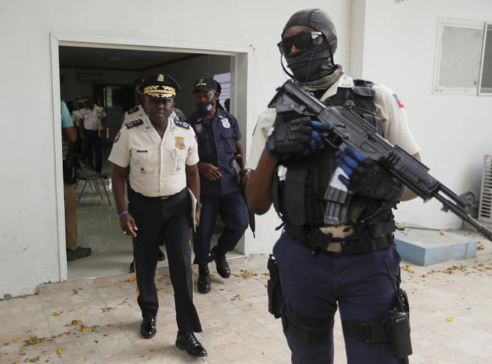Leon Charles, left, Director General of Haiti's Police leaves a room after a news conference at police headquarters in Port-au-Prince, Wednesday, July 14, 2021. Charles gave an updated on the investigation of the July 7 assassination of President Jovenel Moise. (AP Photo/Fernando Llano)