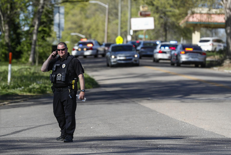 A Knoxville police officer talks on the phone at the scene of a shooting at Austin-East Magnet High School Monday, April 12, 2021, in Knoxville, Tenn. (AP Photo/Wade Payne)