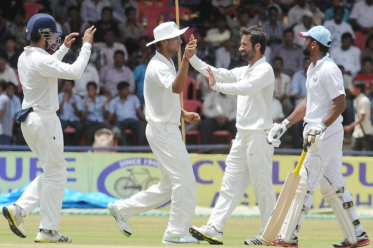 Pervez Rasool of India A celebrates a wicket against West Indies A on Day 2 of their first Test match at the Gangothri Glades Cricket Ground, Mysore, September 26 2013. (IANS)