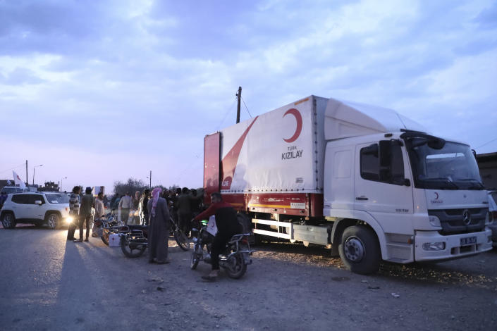 In this image provided by Turkish Red Crescent, Syrians wait for aid being distributed by Turkish Red Crescent in Ras Al-Ayn, Syria, Saturday, Oct. 19, 2019. Turkish Red Crescent says it has delivered humanitarian aid for 2000 people in Ras Al-Ayn, including flour with other food and hygiene materials to follow. The organisation said it also provided aid to Tal Abyad and will continue to do so in areas cleared by the Turkish and the Turkish-backed forces, from fighters from Kurdish People's Protection Units, or YPG. (Fatih Isci/Turkish Red Crescent via AP)