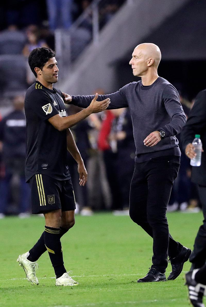 Los Angeles FC's Carlos Vela, left, is hugged by coach Bob Bradley after the team's 3-2 loss to Real Salt Lake during an MLS soccer playoff match Thursday, Nov. 1, 2018, in Los Angeles. (AP Photo/Marcio Jose Sanchez)