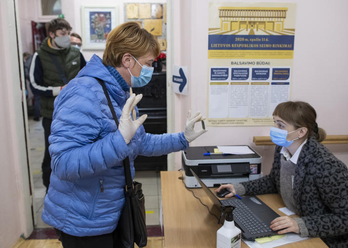 A woman, wearing face masks to protect against coronavirus shows an ID card as she arrives at a polling station during parliamentary elections in Vilnius, Lithuania, Sunday, Oct.11, 2020. Polls opened Sunday for the first round of national election in Lithuania, where voters will renew the 141-seat parliament and the ruling four-party coalition is widely expected to face a stiff challenge from the opposition to remain in office. (AP Photo/Mindaugas Kulbis)