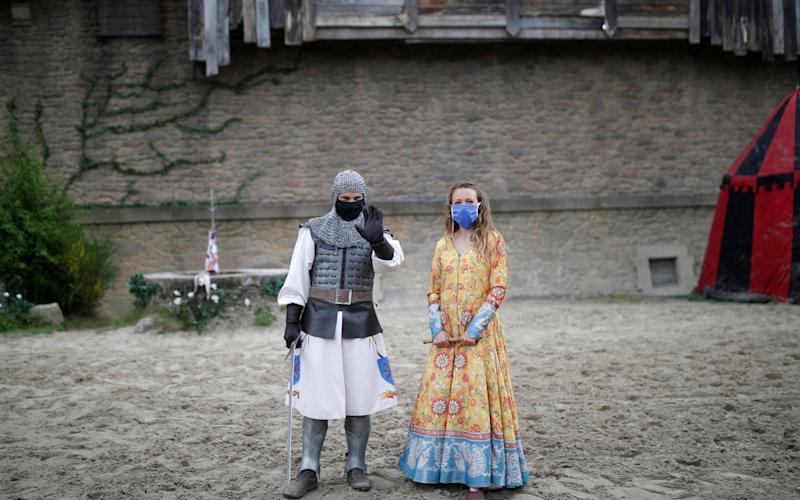 Actors wearing protective masks pose after a rehearsal at French theme park Le Puy du Fou -  Stephane Mahe / REUTERS