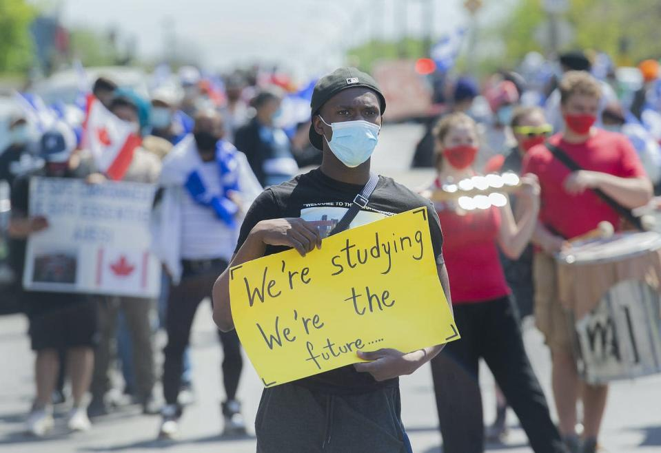 A person holds up a sign at a pro-immigration rally in Montreal.