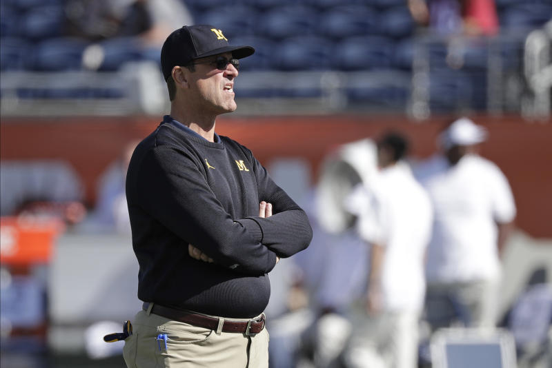 Michigan head coach Jim Harbaugh watches players warm up before the Citrus Bowl NCAA college football game against Alabama, Wednesday, Jan. 1, 2020, in Orlando, Fla. (AP Photo/John Raoux)