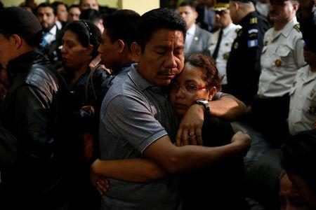 Relatives of a slain policeman react during a homage for their loved one and two colleagues, who were killed during an attack, at the headquarters of the Civil National Police (PNC) in Guatemala City, Guatemala, March 21, 2017. REUTERS/Luis Echeverria