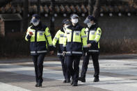 South Korean police officers wearing face masks as a precaution against the coronavirus, walk in Seoul, South Korea, Monday, Jan. 25, 2021. (AP Photo/Lee Jin-man)
