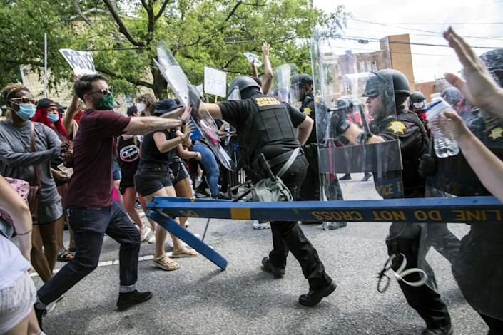 "<span class=""element-image__caption"">Protesters and police clash in Columbia, South Carolina on 31 May.</span> <span class=""element-image__credit"">Photograph: Jason Lee/AP</span>"