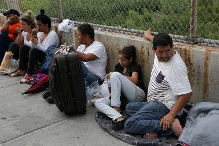 FILE PHOTO: Asylum seekers wait on the Mexican side of the Brownsville-Matamoros International Bridge after being denied entry by U.S. Customs and Border Protection officers near Brownsville