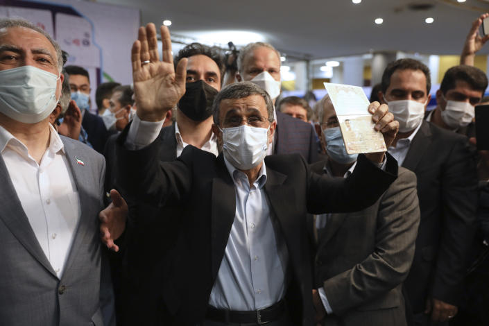 Former President Mahmoud Ahmadinejad, right, waves as he shows his identification document while registering his name as a candidate for the June 18, presidential elections at elections headquarters of the Interior Ministry in Tehran, Iran, Wednesday, May 12, 2021. The country's former firebrand president will run again for office in upcoming elections in June. The Holocaust-denying Ahmadinejad has previously been banned from running for the presidency by Supreme Leader Ayatollah Ali Khamenei in 2017, although then, he registered anyway. (AP Photo/Vahid Salemi)