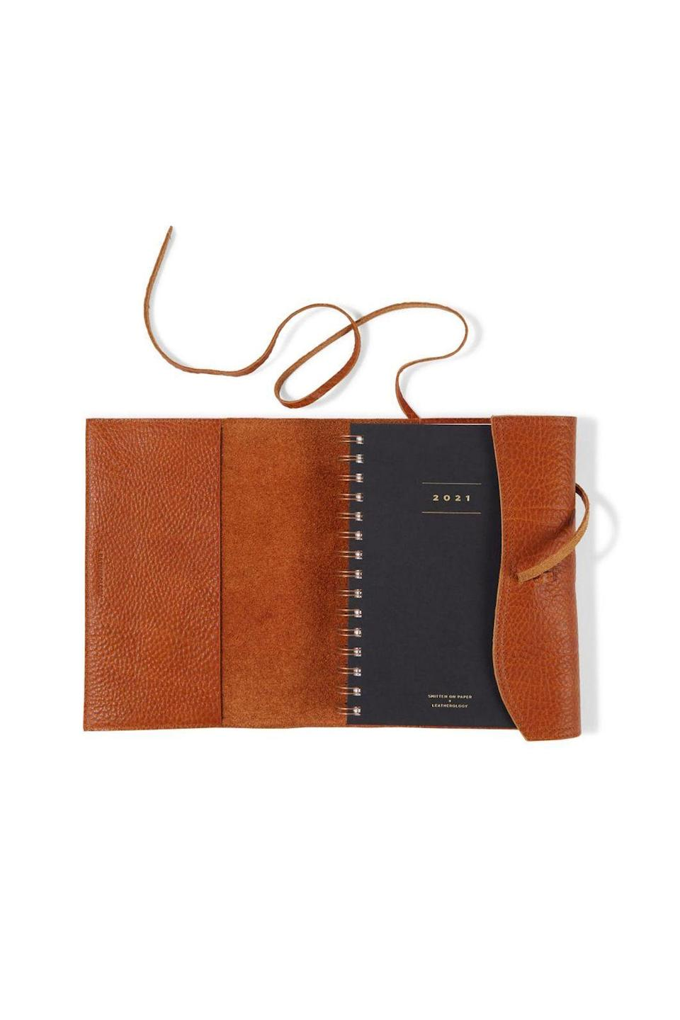 """<p><strong>Leatherology</strong></p><p><strong>$115.00</strong></p><p><a href=""""https://www.leatherology.com/wrap-planner-tan-leather-whiskey/"""" rel=""""nofollow noopener"""" target=""""_blank"""" data-ylk=""""slk:SHOP IT"""" class=""""link rapid-noclick-resp"""">SHOP IT</a></p><p>Leatherology's wrap 2021 planner was made for those who can't leave home without their to-do list. Customize the vegan leather cover with a chic monogram on the front, and keep it for years to come—just swap the insert when 2022 comes around.</p>"""
