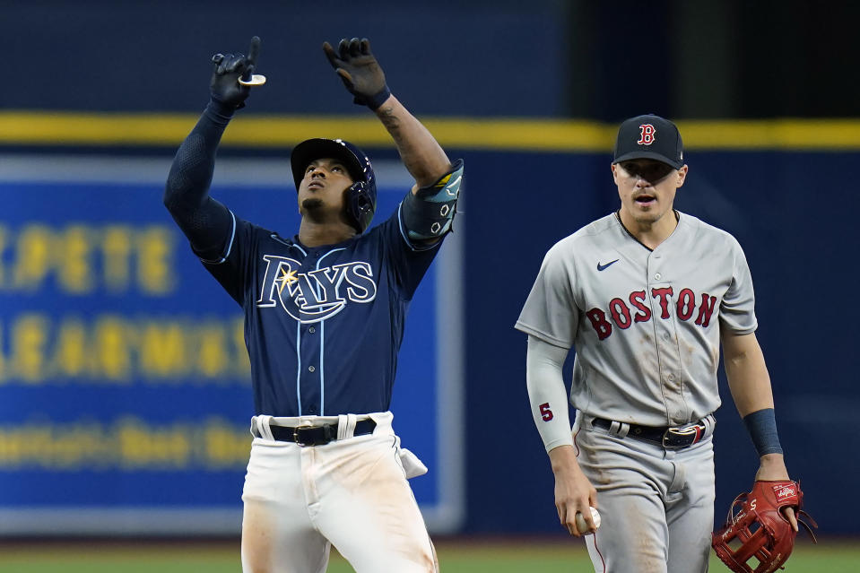 Tampa Bay Rays' Wander Franco, left, celebrates his double off Boston Red Sox relief pitcher Josh Taylor during the seventh inning of a baseball game Tuesday, June 22, 2021, in St. Petersburg, Fla. Looking on Boston's Kike Hernandez. (AP Photo/Chris O'Meara)