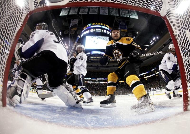 In this photo taken with a fisheye lens, Boston Bruins' Gregory Campbell (11) skates through the crease of Tampa Bay Lightning goalie Dwayne Roloson during the third period of Tampa's 5-2 win in Game 1 of an NHL hockey Stanley Cup Eastern Conference final playoff series, Saturday, May 14, 2011, in Boston. (AP Photo/Winslow Townson)