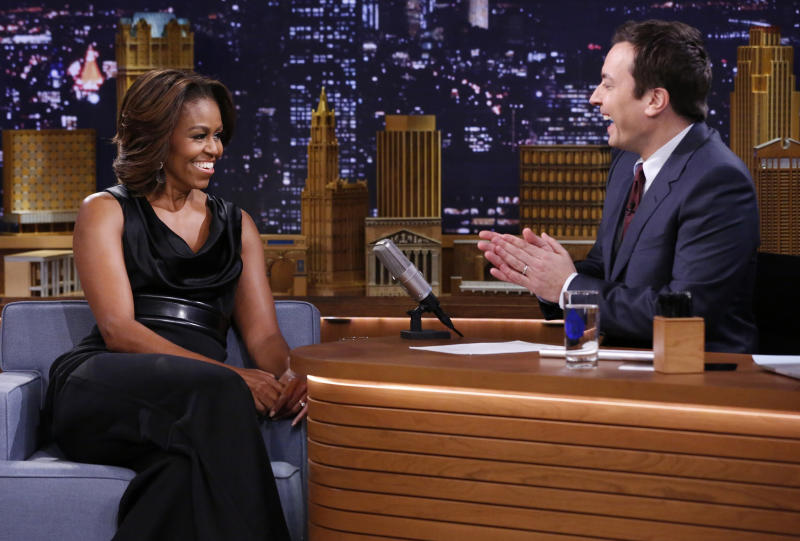"FILE- In this Feb. 20, 2014 photo provided by NBC, host Jimmy Fallon applauds first lady Michelle Obama on the set of ""The Tonight Show Starring Jimmy Fallon,"" in New York. Aside from Fallon wanting to do the show in New York City, NBC could have viewed a 30 percent tax break as incentive to bring the show back from the West Coast after 40 years. The tax credit, designed to lure certain types of programming to New York, can potentially save the network $20 million dollars a year. (AP Photo/NBC, Lloyd Bishop, File)"