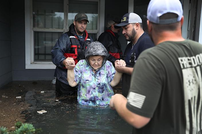 <p>Volunteer rescuer workers help a woman from her home that was inundated with the flooding of Hurricane Harvey on Aug. 30, 2017 in Port Arthur, Texas. (Photo: Joe Raedle/Getty Images) </p>