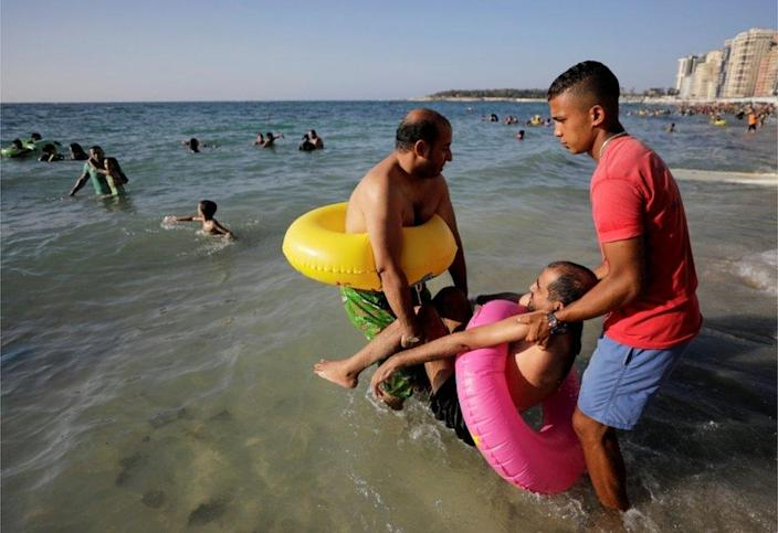 Beach workers help a man enter the sea.