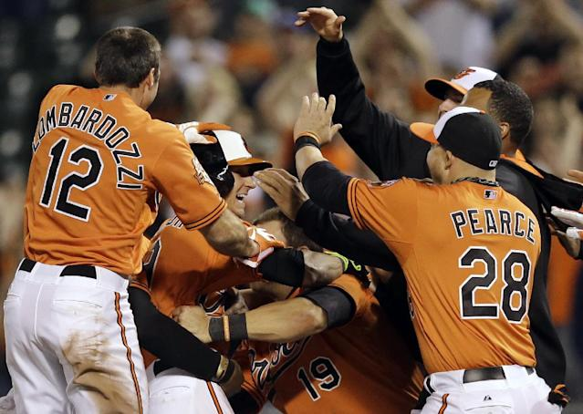 Baltimore Orioles' David Lough, in batting helmet, celebrates with teammates after hitting a game-winning single in the 12th inning of a baseball game against the Toronto Blue Jays, Saturday, April 12, 2014, in Baltimore. Stephen Lombardozzi scored on the play, and Baltimore won 2-1. (AP Photo/Patrick Semansky)
