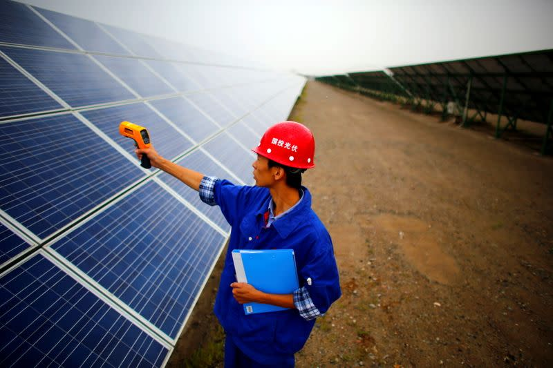 FILE PHOTO: A worker inspects solar panels at a solar farm in Dunhuang