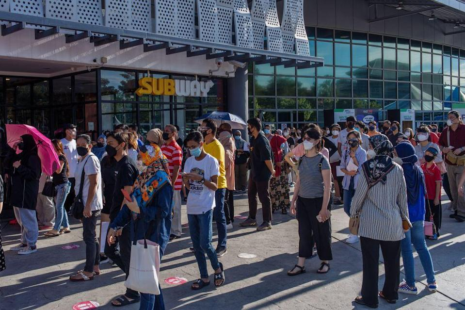 People queue as they wait to receive their Covid-19 jab at the Axiata Arena in Bukit Jalil September 23, 2021. — Picture by Shafwan Zaidon