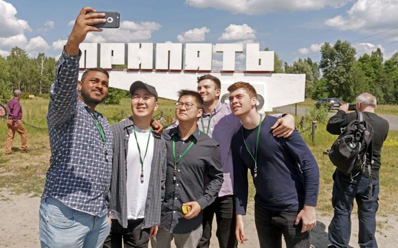 Tourists take a selfie in the ghost town of Pripyat, which has seen visitor numbers skyrocket after the HBO series about the 1986 meltdown at the Chernobyl nuclear power plant there - Bloomberg